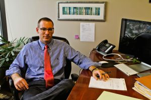 Stephen J. Haedicke sitting at his desk in his law office